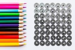 Bleistifte und Knöpfe über weißem Hintergrund Stockbild