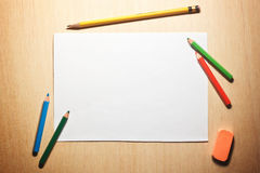 Bleistifte und leeres Papier auf hölzerner Tabelle Lizenzfreies Stockbild