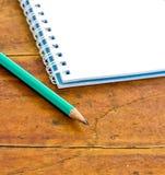Bleistifte und Notizbuch auf einem hölzernen Stockfoto