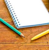 Bleistifte und Notizbuch auf einem hölzernen Stockbilder