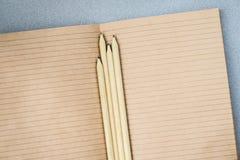 Bleistifte und offenes Notizbuchpapier vom Kraftpapier, Draufsicht, Beschaffenheit Platz für Text, das Konzept des Beginnens der  Stockbild