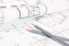 Bleistifte und Papiertechnik bringen Zeichnungen und Pläne unter Stockfotografie