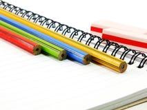 Bleistifte und Radiergummi nah oben auf leerem Papier Stockfotografie