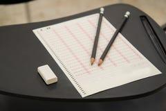 Bleistifte und Radiergummi setzten an optisches Markierungserkennungsblatt in Prüfungsraum ein Lizenzfreie Stockbilder