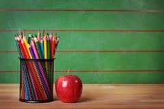 Bleistifte und roter Apfel Stockbilder