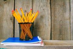 Bleistifte und Schreibenbücher auf einem hölzernen Regal Lizenzfreie Stockfotografie