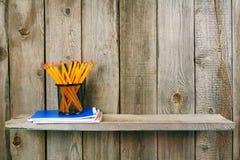 Bleistifte und Schreibenbücher auf einem hölzernen Regal Stockfoto