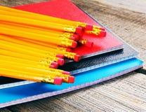 Bleistifte und Schreibenbücher Auf hölzernem Hintergrund Lizenzfreies Stockfoto