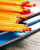 Bleistifte und Schreibenbücher Auf hölzernem Hintergrund Lizenzfreie Stockbilder