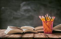 Bleistifte und Stapel von Büchern Stockfotografie