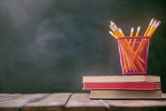 Bleistifte und Stapel von Büchern Stockfotos