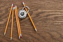 Bleistifte und Verschluss auf Holzoberfläche Stockbilder