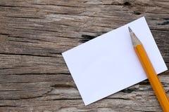 Bleistifte und weiße Pappe auf altem Bretterboden Lizenzfreies Stockbild