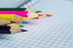 Bleistifte von verschiedenen Farben auf einem offenen Notizbuch Lizenzfreie Stockfotografie