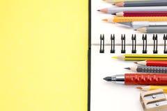 Bleistifte von verschiedenen Farben und gewundener Notizblock auf gelbem backgro Lizenzfreie Stockfotografie