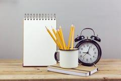 Bleistifte, Wecker und Notizbuch auf Holztisch Unternehmensplanungsprozeß Stockbild