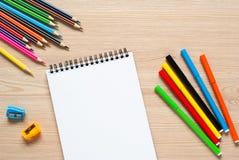 Bleistifte, Zeichenstifte und Notizbuch auf einem Schreibtisch Stockfotos