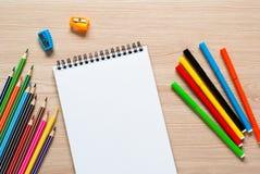 Bleistifte, Zeichenstifte und Notizbuch auf einem Schreibtisch Stockbild