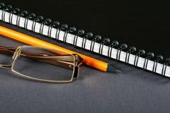 Bleistiftgläser und ein Schreibenbuch Lizenzfreie Stockbilder