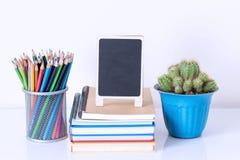 Bleistiftkasten auf Buchstapel und Blumentopf auf weißem Tabelle workspac Lizenzfreie Stockbilder
