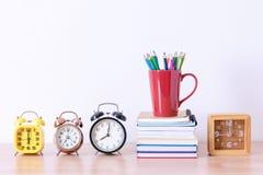Bleistiftkasten auf Buchstapel und Wecker auf Holztisch worksp Lizenzfreie Stockbilder