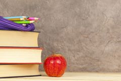 Bleistiftkasten auf einem Stapel von Büchern mit einem Apfel Lizenzfreies Stockbild