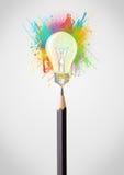 Bleistiftnahaufnahme mit farbiger Farbe spritzt und Glühlampe Lizenzfreie Stockfotos