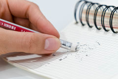 Bleistiftradiergummi, Bleistiftradiergummi, der einen schriftlichen Fehler auf einem Blatt Papier, der Löschung, korrekten und de Lizenzfreie Stockfotografie