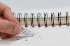 Bleistiftradiergummi, der einen schriftlichen Fehler auf einem Anmerkungsbuch, einer Schule und einem Fehlerkonzept entfernt Lizenzfreies Stockbild