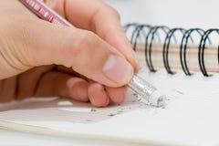 Bleistiftradiergummi, der einen schriftlichen Fehler auf einem Anmerkungsbuch, einer Schule und einem Fehlerkonzept entfernt Stockfoto