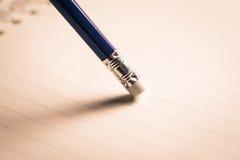 Bleistiftradiergummi, der einen schriftlichen Fehler auf einem Blatt Papier, De entfernt Lizenzfreies Stockbild