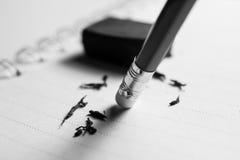 Bleistiftradiergummi, der einen schriftlichen Fehler auf einem Blatt Papier, De entfernt Lizenzfreies Stockfoto