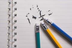 Bleistiftradiergummi, der einen schriftlichen Fehler auf einem Blatt Papier, De entfernt Lizenzfreie Stockfotos
