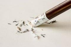 Bleistiftradiergummi, der einen schriftlichen Fehler auf einem Blatt Papier entfernt Stockbild