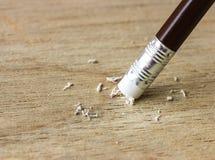 Bleistiftradiergummi, der einen schriftlichen Fehler auf Holz entfernt Stockfotografie