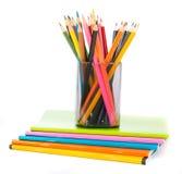 Bleistiftschale mit Zeichenstiften auf Übungsbüchern Lizenzfreie Stockbilder