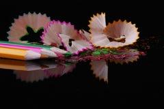 Bleistiftschnitzel und abgleichende farbige Bleistifte Stockfotos