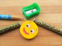 Bleistiftspitzer, Bleistifte, Bleistiftstift und Radiergummi auf hölzernem Hintergrund Lizenzfreie Stockfotos