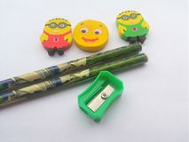Bleistiftspitzer, Bleistifte und Radiergummis auf weißem Hintergrund Lizenzfreie Stockfotos