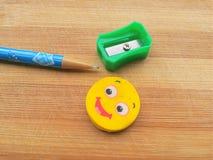 Bleistiftspitzer, Bleistiftstift und Radiergummi auf hölzernem Hintergrund Stockbild