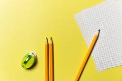 Bleistiftspitzer, Liste für das Notieren, Bleistifte auf einem gelben Hintergrund Bürothema Stockbilder