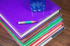 Bleistiftspitzer mit kleinem Bleistift auf Stapel Büchern Stockbild