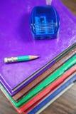 Bleistiftspitzer mit kleinem Bleistift auf Stapel Büchern Stockbilder
