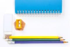 Bleistiftspitzer, Radiergummi, Notizbuch und Bleistifte auf Whit Lizenzfreie Stockbilder