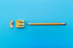 Bleistiftspitzer und Bleistift auf einem Blatt Papier Blau Stockbild