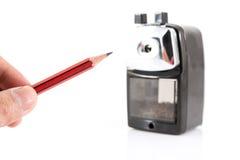 Bleistiftspitzer und Bleistift auf weißem Hintergrund Stockfotografie