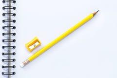 Bleistiftspitzer und Bleistift lokalisiert auf Notizbuchhintergrund Stockfoto