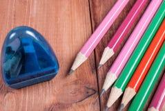 Bleistiftspitzer und Bleistifte auf dem hölzernen Hintergrund Lizenzfreie Stockfotos
