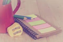 Bleistiftspitzer und Farbbleistift auf Buch Stockfotografie