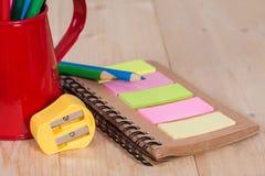 Bleistiftspitzer und Farbbleistift auf Buchanmerkung Stockbilder